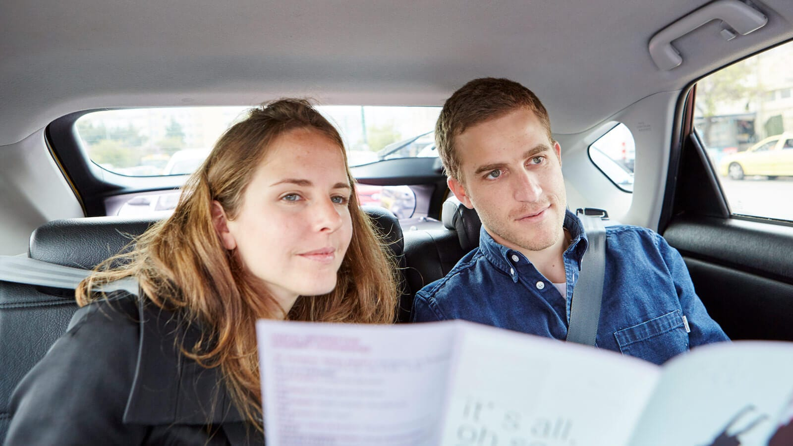 man and woman in the back seats of a taxi checking a map