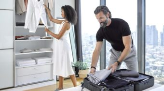 man and woman packing a suitcase in a light, beautiful bedroom