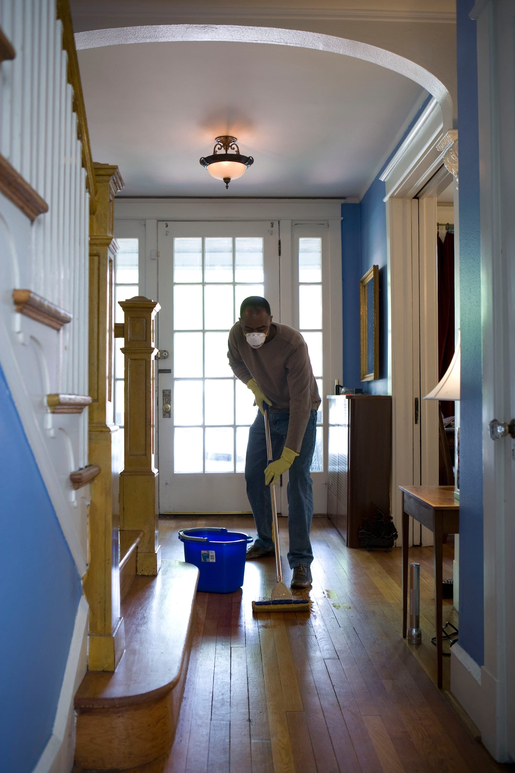 african american man cleaning hallway in vacation rental home