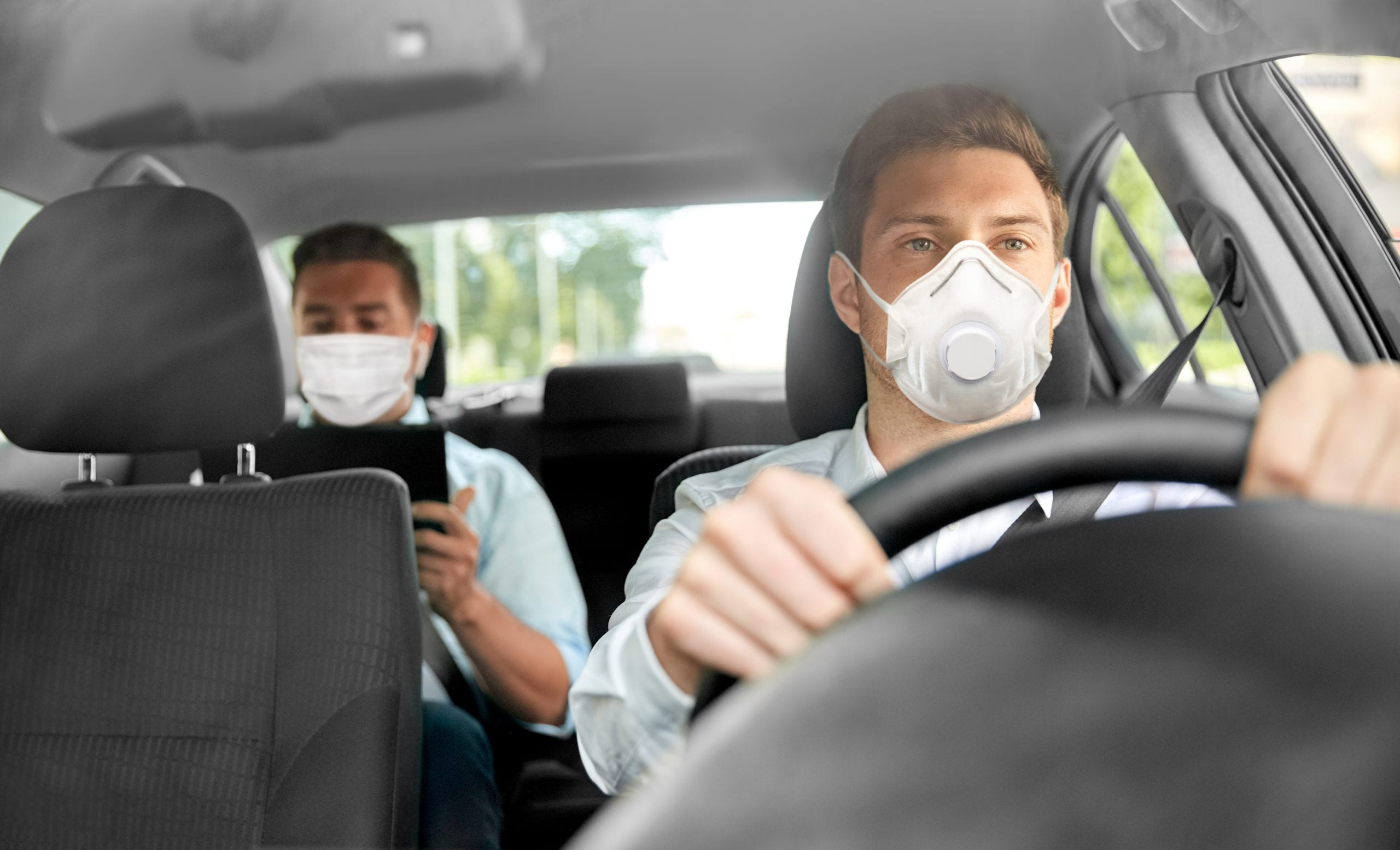 driver and passenger in car wearing protective masks