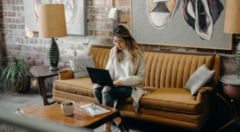 woman working on a laptop sitting on couch in a vacation rental home