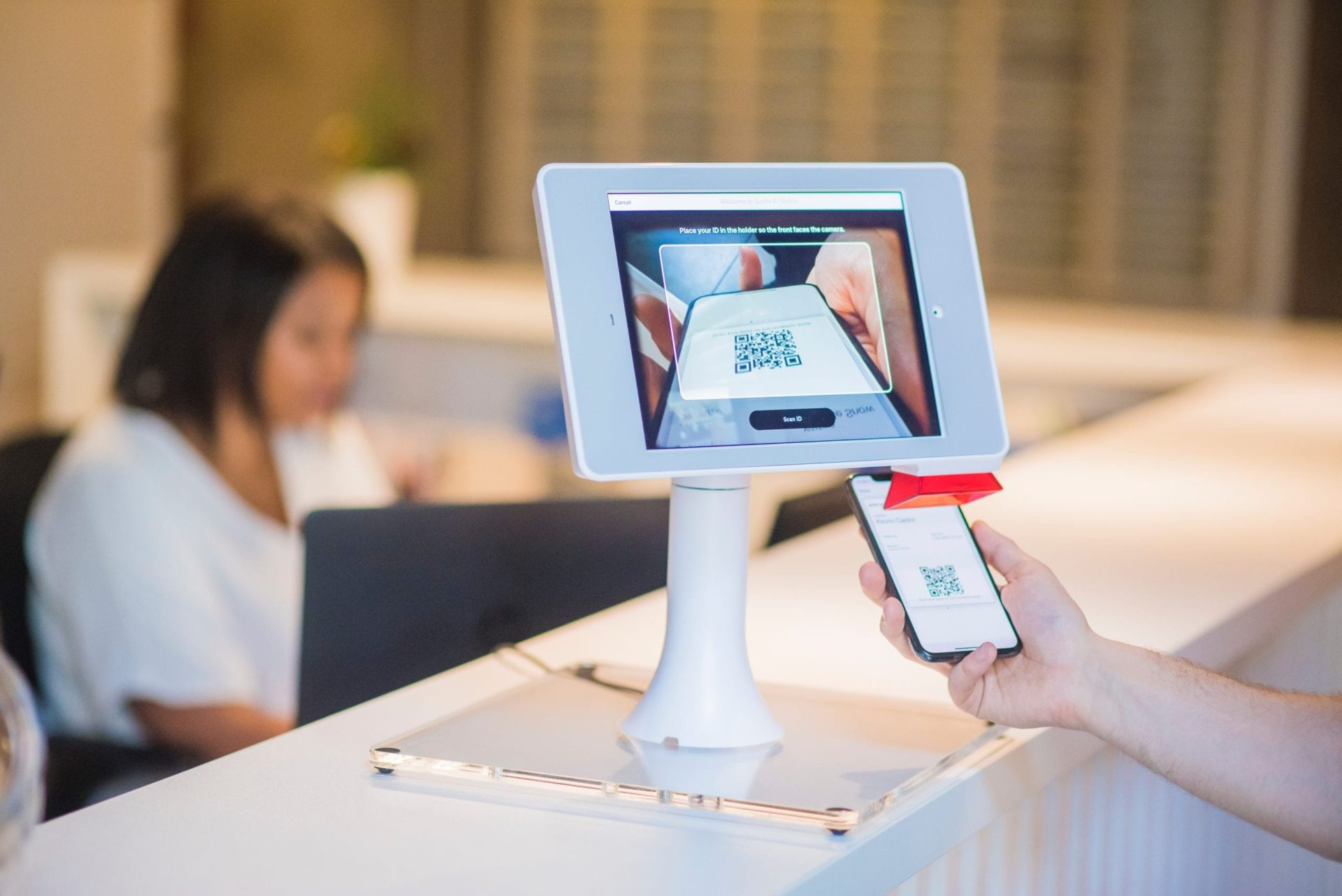 person performing contactless check-in at hotel front desk using their smartphone