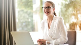 woman in front of laptop looking up and smiling